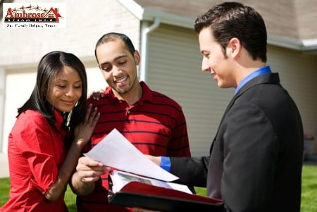 male real estate agent with couple in front of home