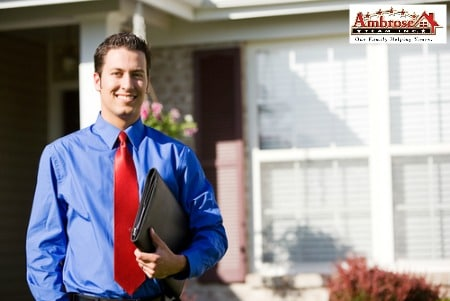 male real estate agent outside house