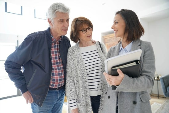 55+ couple looking at patio home with real estate agent