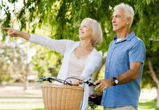 55+ woman and man with bike, woman is pointing to something out of shot and smiling
