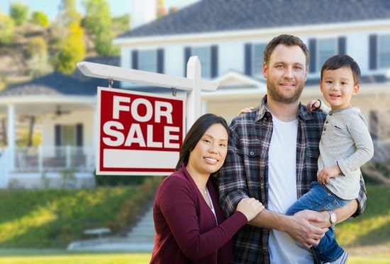man, woman, and child standing in front of home with for sale sign