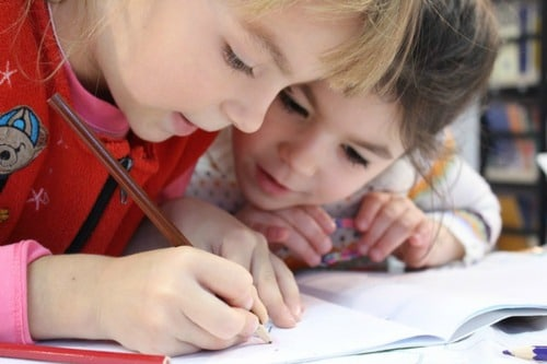 two elementary school aged girls drawing with a pencil