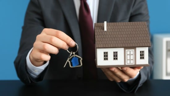 man in suit holding keys and model house - real estate market concept