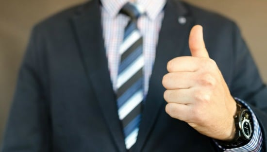 man in suit holding thumb up