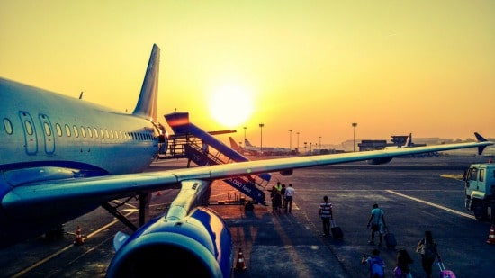 people boarding a plane at sunset on the runway