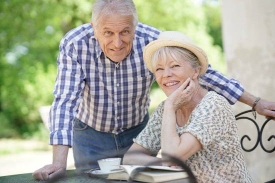 senior woman reading book with man standing near