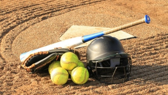 softballs, baseball glove, bat, helmet, and base on a dirt field