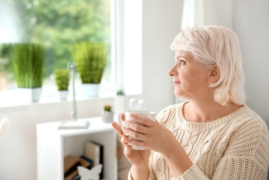 woman drinking coffee and looking out bright window