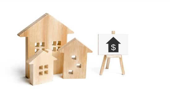 3 wooden houses of various sizes next to a stand with a dollar sign