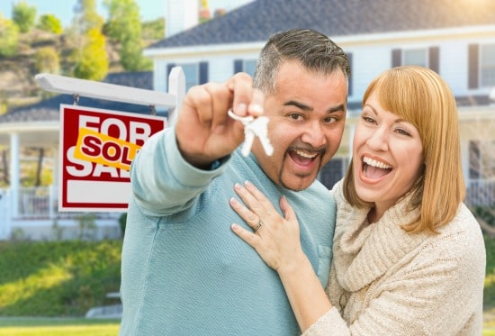 man and woman embracing and smiling with man holding house keys