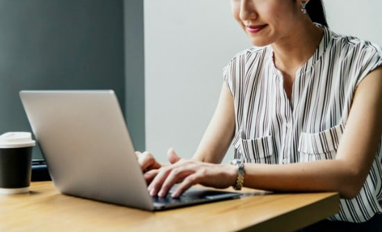 Woman sitting at laptop - real estate market report looking concept