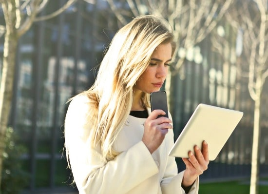 Woman looking at tablet and holding phone